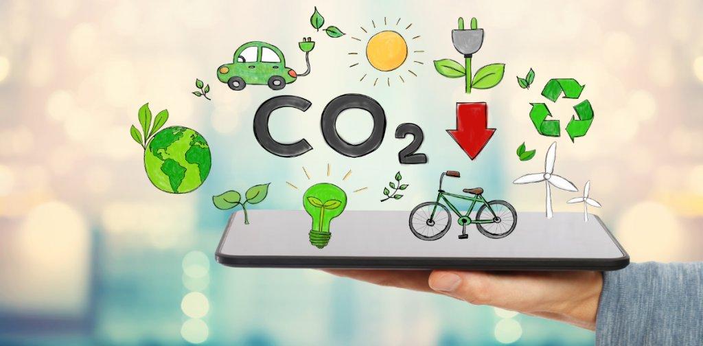 """Sur une main est déposée une tablette qui numérise une voiture verte, un vélo vert, des éoliennes, la planète terre, une ampoule, un soleil, une prise électrique, le logo recyclable. Au milieu de tous ces éléments est écrit """"CO2""""."""