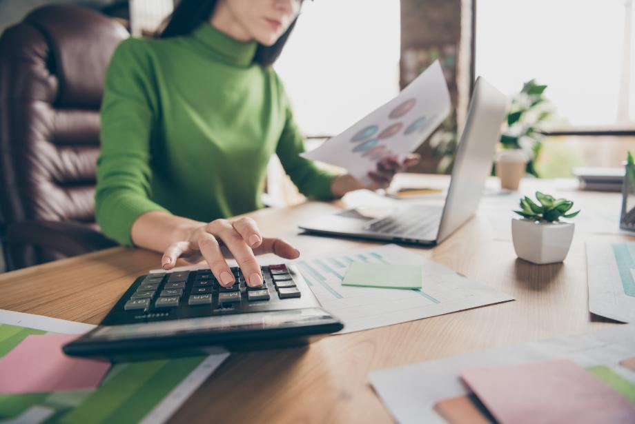 Une femme avec un haut vert assise à son bureau devant son ordinateur tient dans sa main gauche des feuilles de papier et utilise sa calculatrice avec sa main droite