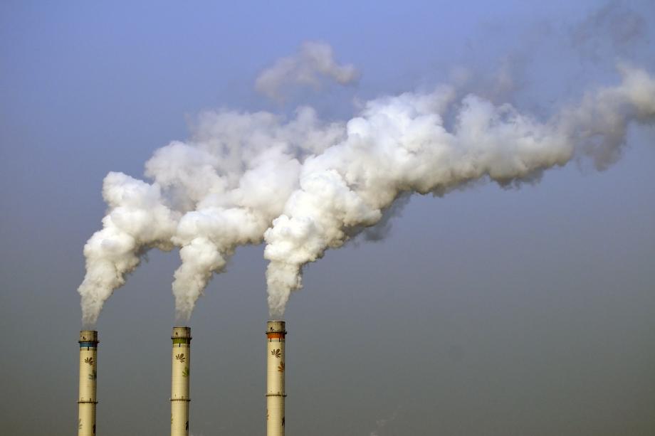 Trois cheminées d'une usine qui relâchent de la fumée dans l'air.