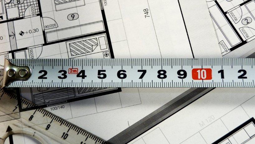Un mètre à mesurer est posé sur des plans de maison à coté d'une règle en plastique transparente.
