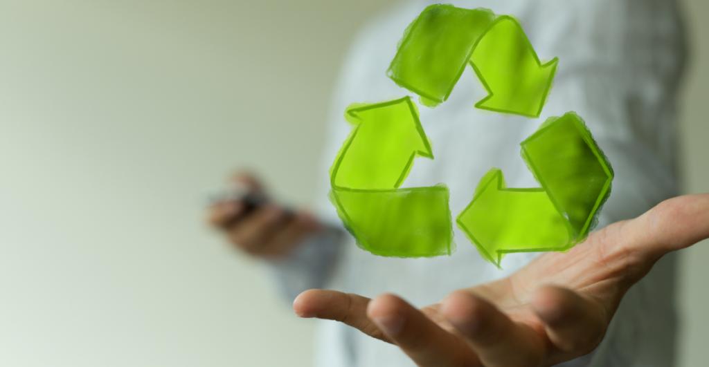 L'image représente une personne qui tient dans sa main le logo vert du recyclage.