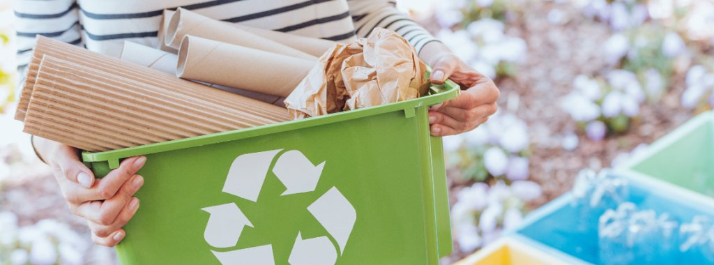 Une personne tient un bac vert où y est dessiné le logo du recyclage en blanc. A l'intérieur s'y trouvent des déchets recyclables. Derrière elle on y aperçoit les poubelles jaune, bleue et verte.