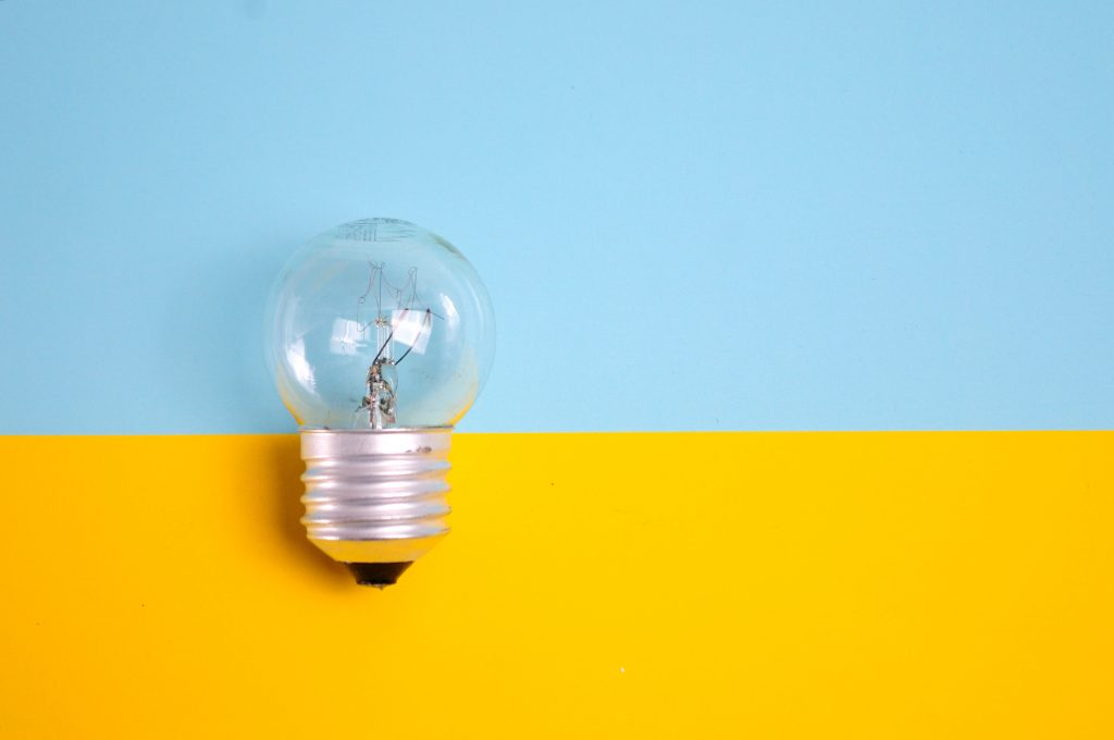 Le fond de l'image est moitié bleu en haut et moitié jaune en bas. à gauche de l'image est posé une ampoule.