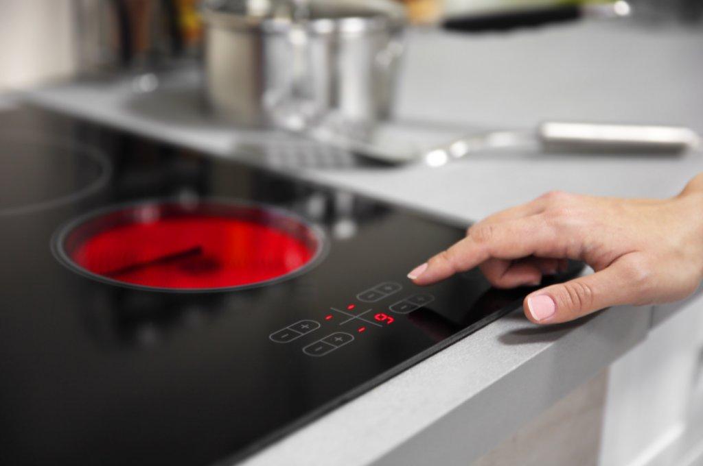 Une main touche les boutons d'une plaque à induction pour l'allumer.
